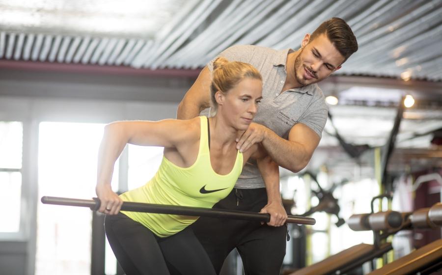 Personal Trainer Farris Elghadi korrigiert eine Frau beim Training