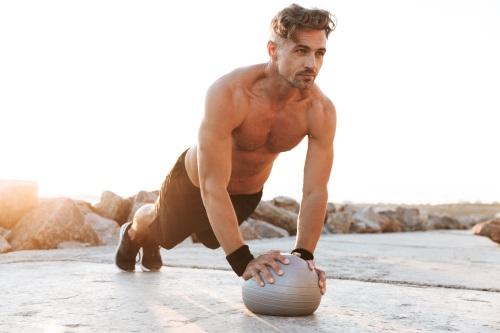 Mann oberkörperfrei trainiert mit Ball beim Personal Training