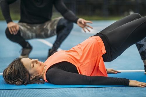 Frau macht Hüftbrücke mit Personal Trainer im Hintergrund