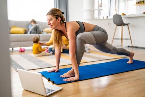 Frau trainiert auf Matte vor ihrem Laptop, im Hintergrund sind Kinder