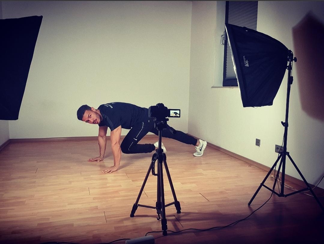 Online Personal Trainer Farris Elghadi trainiert in einem Zimmer vor einer Kamera mit Stativ